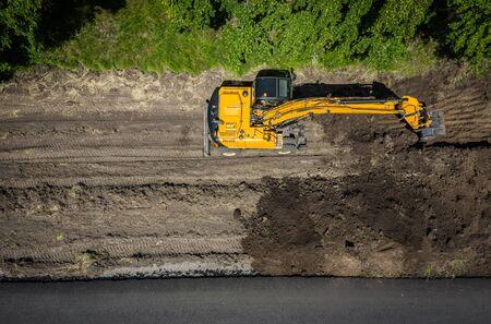 Roadwork excavator machinery used in road repairs of a highway top view