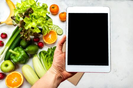 Order, delivery food online. Female hand holding the tablet computer with blank screen over fresh vegetables. Close-up