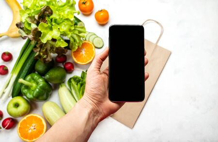 Order, delivery food online. Female hand holding smartphone with blank screen for your text over organic vegetables. Close-up 写真素材