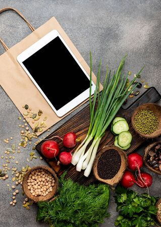 Order food online. Organic food products on a wooden board with tablet computer and shopping paper bag top view.