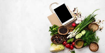 Order, delivery food. Organic food products on a wooden board with tablet computer and shopping paper bag on white background with copy space. Banner