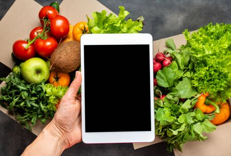 Delivery food. Female hand holding the tablet computer with blank screen over boxes with fresh organic products.