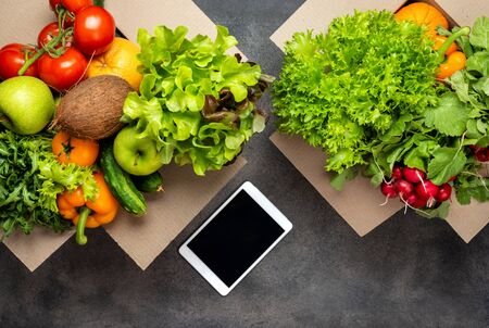 Order and delivery food. organic products in boxes and tablet computer on the table on grey background. Top view
