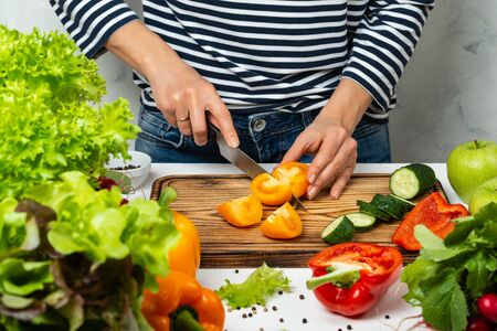Woman cooking healthy vegan diet food. Cutting vegetables in the kitchen.