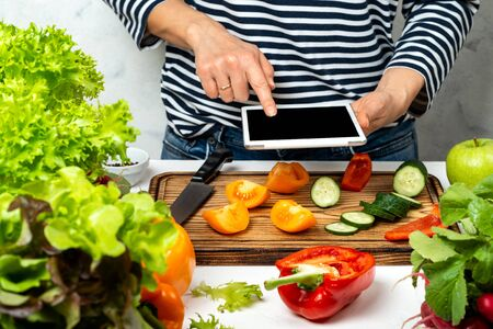 Woman cooking and holding tablet computer with blank screen in hand. Cutting vegetable ingredients and following recipe from the internet.