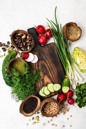 Wooden cutting board with fresh vegetables, ingredients for cooking vegan food. Top view