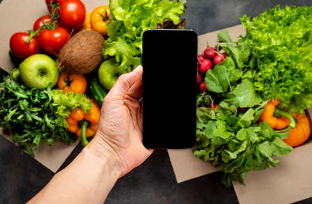 Female hand with smartphone and full boxes of different fresh organic vegetables. Delivery or Order food online concept.