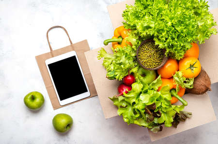 Box full of fresh organic products, tablet computer with blank screen and paper shopping bag. Delivery order food concept. Top view.