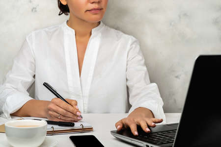 Online education. Female student sitting at the table in front of laptop and writing. 写真素材