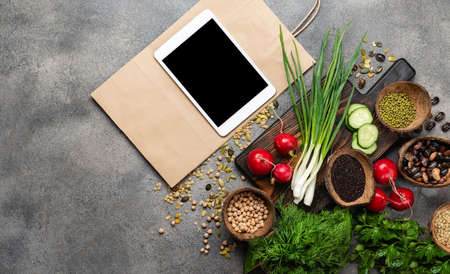 Tablet computer, paper shopping bag, different healthy products. Top view with place for text. 写真素材