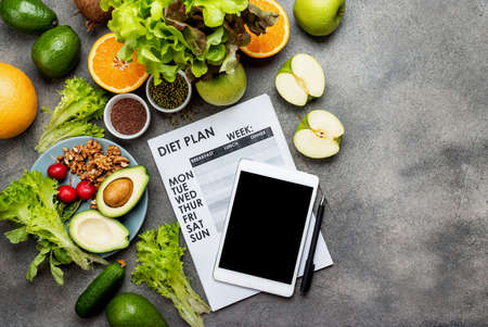 Diet meal plan concept. Tablet computer with blank screen and weight loss program on the sheet, fresh food on the table. Top view.