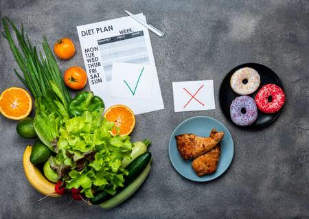 Choice between junk food and diet healthy vegan food with diet plan. Top view