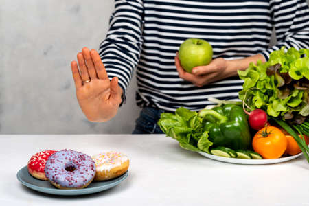 woman refuse junk food but healthy food choice. Diet concept