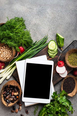 Healthy balanced vegan food concept. Tablet computer, notebook, fresh vegetables, herbs, cereal and nuts. Veggie cooking