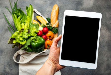 Tablet computer with blank screen in female hand above shopping bag full of healthy food. Order food delivered online concept 写真素材