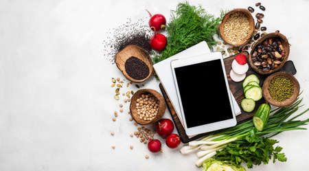 Tablet computer with blank screen and notebook with fresh vegetables on the chopping board. Top view with place for text