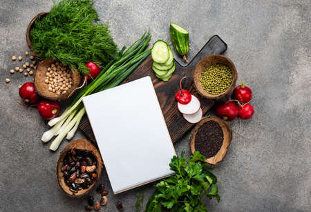 Blank notepad and fresh vegetables ingredients for veggie cooking