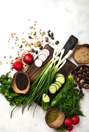Raw vegetables greenery cereals beans on the chopping board