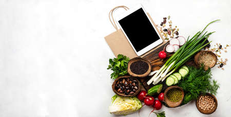 Tablet computer and shopping paper bag with ingredients for cooking healthy food. Top view with place for text