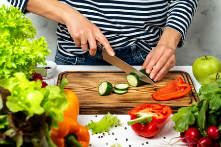 Woman cutting vegetables in the kitchen. Cooking healthy diet food concept