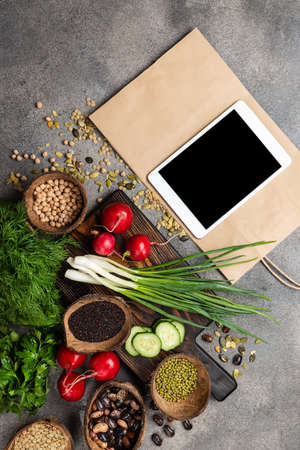 Organic food products on a chopping board with tablet computer and shopping paper bag top view. 写真素材