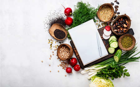 Open blank recipe book with healthy vegan ingredients for cooking and chopping board top view.