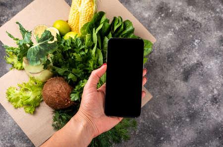 Smartphone in female hand and full box of fresh organic vegetables.