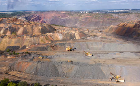 open pit quarry with a lot of equipment at work aerial view.