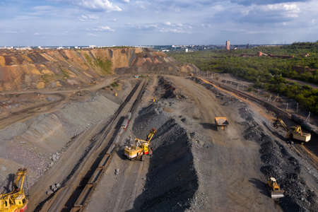 Excavator and heavy mining dump trucks in a limestone quarry, loading of stone ore, industrial panorama. 写真素材