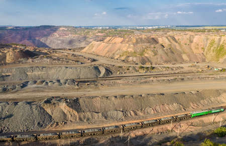 Cargo train carrying iron ore on the opencast mining quarry aerial view