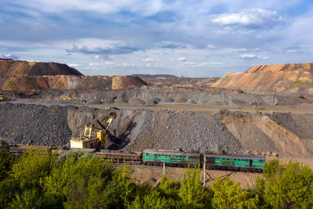 Cargo train carrying iron ore on the opencast mining quarry