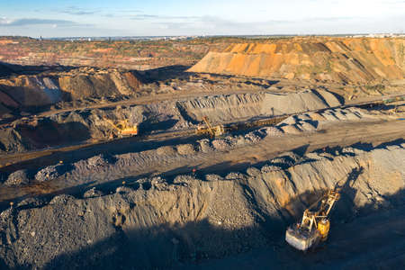 Quarry extracting iron ore with heavy trucks excavators diggers and locomotives aerial view.