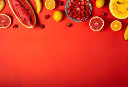 Border of fruits and vegetables on the red background. Top view with copy space