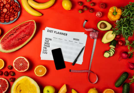 Smartphone and diet plan with measuring tape and set of healthy food. Top view Banco de Imagens