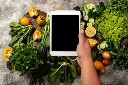 Male hand holding the tablet computer with blank screen over fresh vegetables