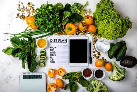 Tablet computer Diet plan and set of healthy food with kitchen scale