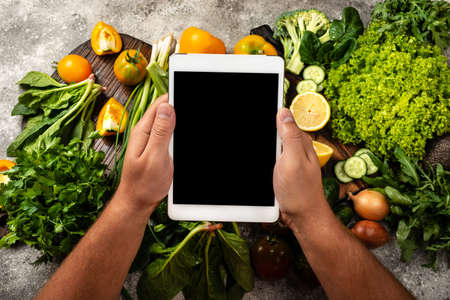 Male hands are holding the tablet computer with blank screen over fresh vegetables