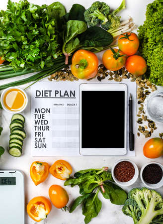 Lose weight concept. Tablet computer Diet plan and set of healthy food with kitchen scale