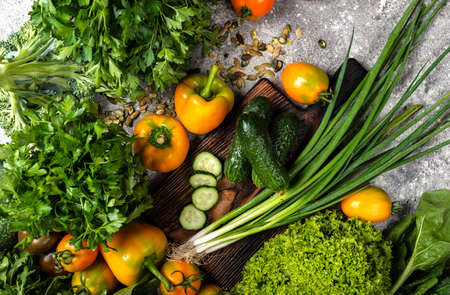 Vegetables and greens with chopping board on the table. Top view. Banco de Imagens