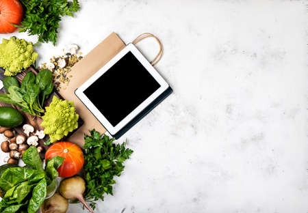 Online grocery shop concept. Tablet computer and shopping paper bag with different vegetables and greens. Top view