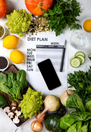 Lose weight concept. Smartphone Diet plan and set of healthy food 版權商用圖片