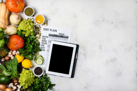 Tablet computer Diet plan and set of different vegetables and greens. 版權商用圖片