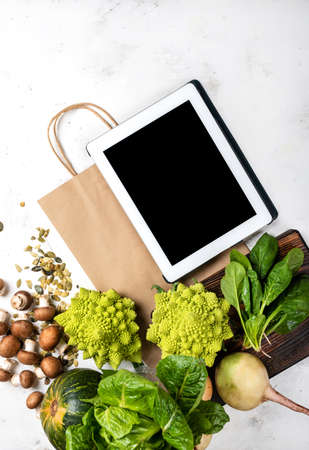 Tablet computer and shopping paper bag with vegetables and greens. Top view