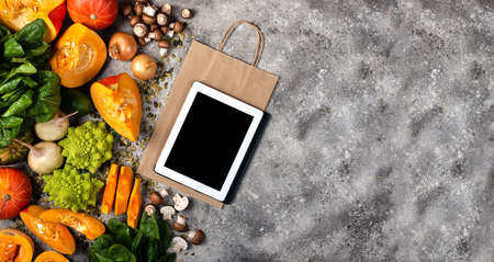 Online grocery shop concept. Tablet computer and shopping paper bag with pieces of pumpkin Different vegetables and greens. Banner Top view.