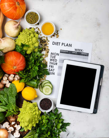 Tablet computer Diet plan on the sheet and different vegetables and greens.