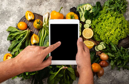 Order Delivery food online concept. Male hands are holding the tablet computer with blank screen over fresh vegetables. Close-up