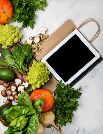 Online grocery shop concept. Tablet computer and shopping paper bag with different vegetables