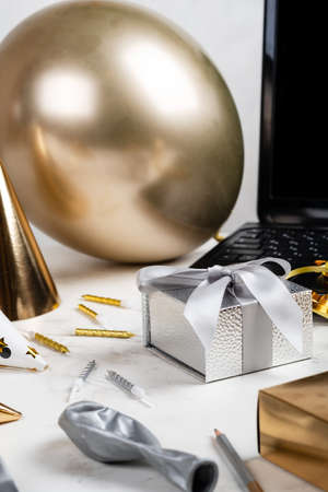 Online celebration concept. Silver festive box and laptop Balloon Other accessories on the white table
