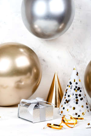 Birthday festive concept Silver gifts box and golden silver balloons with party hats