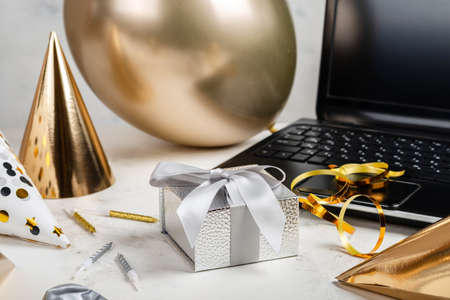 Online celebration concept. Silver festive box and laptop with balloon and party hats on the white table Zdjęcie Seryjne